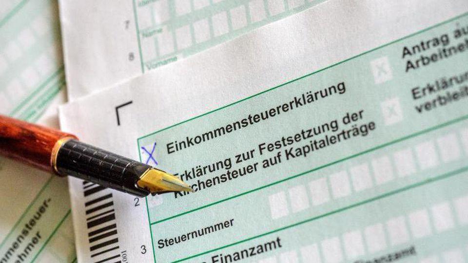 Steuerformulare und Füllfederhalter liegen auf einem Tisch. Foto: Hans-Jürgen Wiedl/dpa-Zentralbild/dpa/Illustration