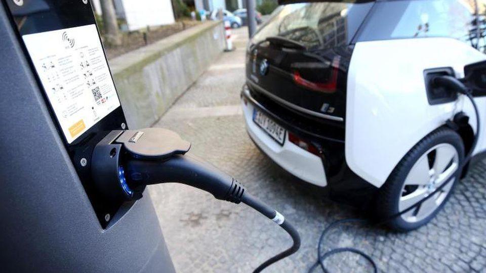 Ein Elektroauto wird mit Strom beladen. Foto: Roland Weihrauch/dpa/Archivbild