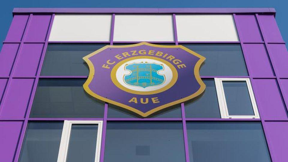 Das Logo von Erzgebirge Aue an der Fassade des Heimstadions. Foto: Robert Michael/Archivbild