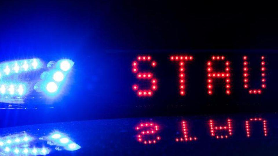"""Blaulicht und der Schriftzug """"Stau"""" auf einem Fahrzeug der Polizei. Foto: Monika Skolimowska/zb/dpa/Symbolbild"""