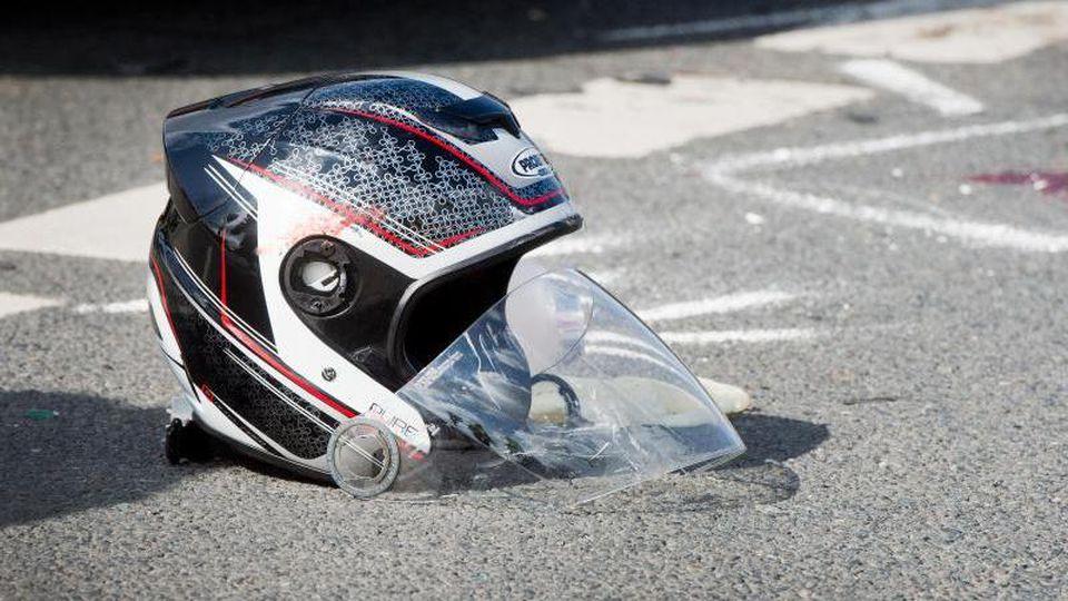 Ein beschädigter Motorradhelm liegt nach dem Unfall auf dem Boden. Foto: Julian Stratenschulte/dpa/Symbolbild