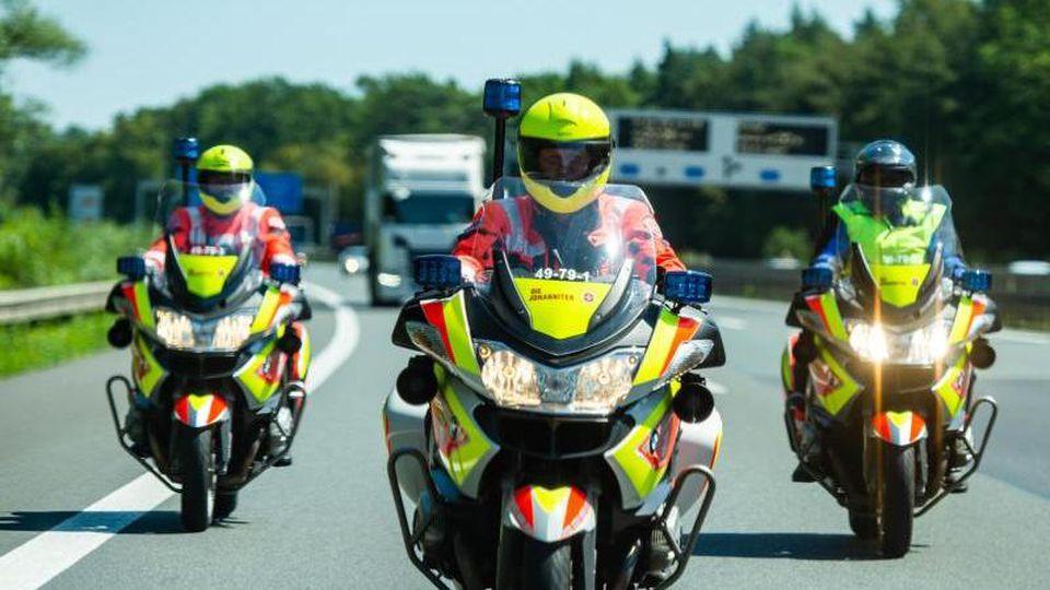 Drei Johanniter-Stauhelfer fahren mit ihren Motorrädern auf der Autobahn. Foto: Christophe Gateau