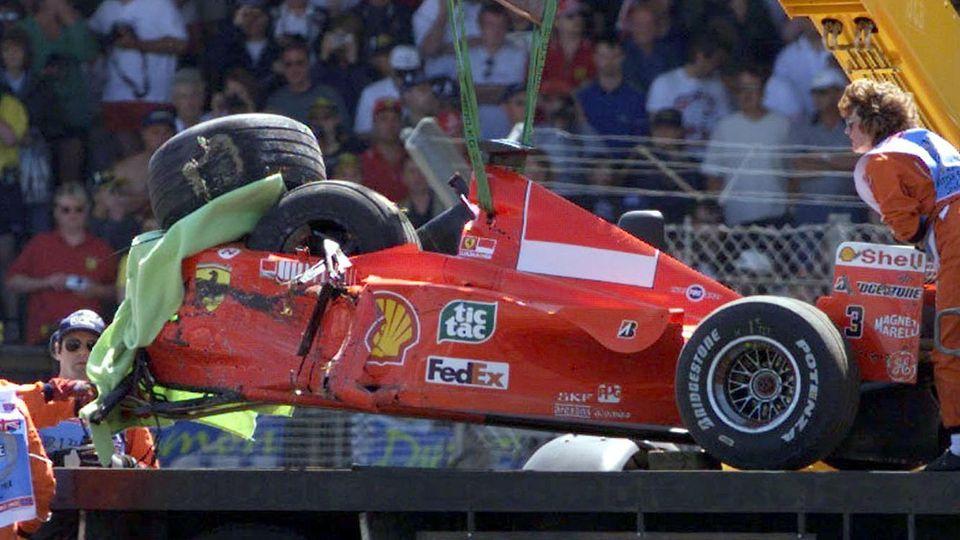 ARCHIV - 10.07.1999, Silverstone: Der zerstörte Formel-1-Rennwagen des Ferrari-Piloten Michael Schumacher wird nach seinem schweren Unfall in der Stowe-Kurve unmittelbar nach dem Start zum 50. Großen Preis von England auf einen Abschleppwagen gehoben