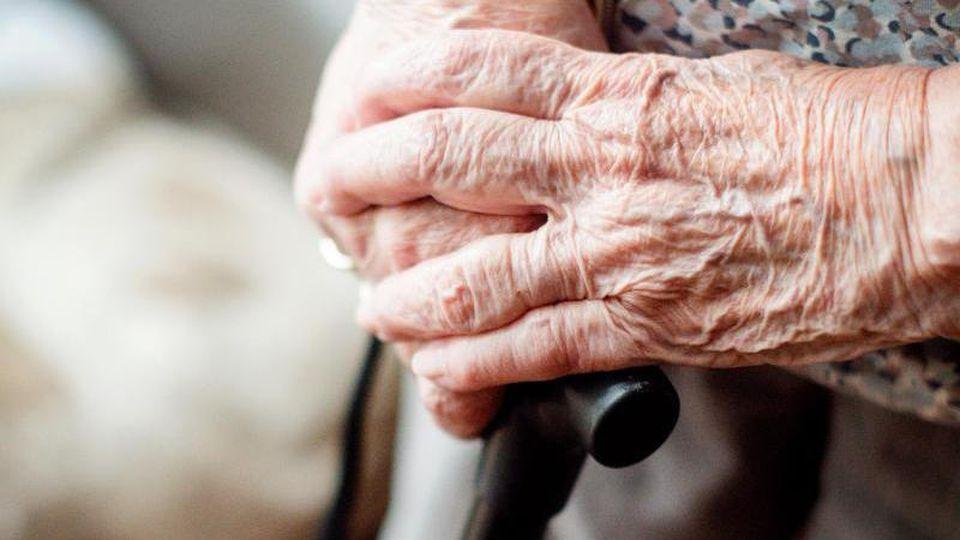 Die Hände einer alten Frau auf einem Gehstock. Foto: Jana Bauch/dpa/Archivbild