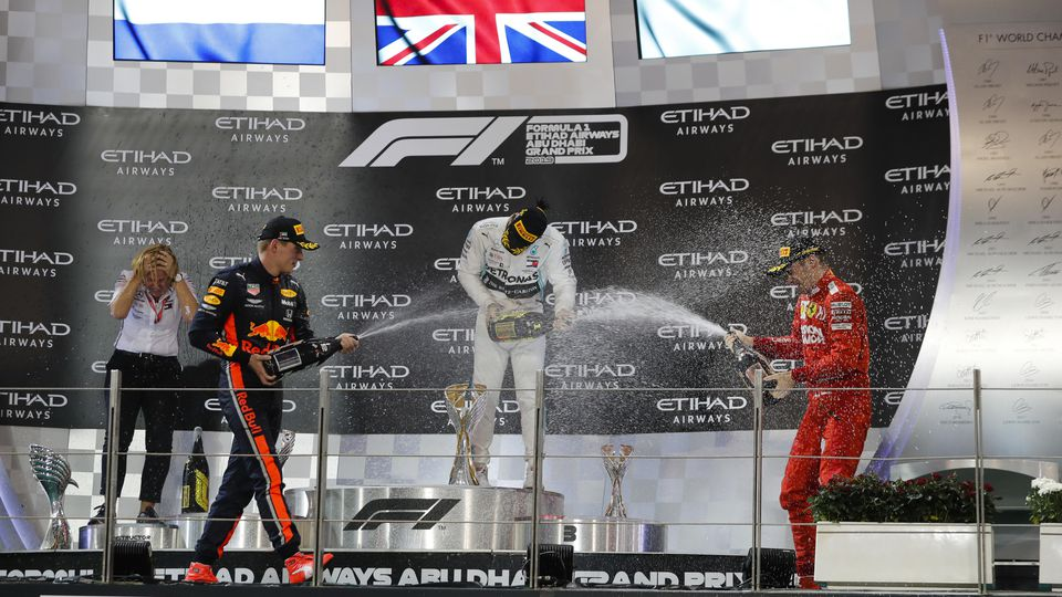 2019 Abu Dhabi GP YAS MARINA CIRCUIT, UNITED ARAB EMIRATES - DECEMBER 01: Max Verstappen, Red Bull Racing, 2nd position, Lewis Hamilton, Mercedes AMG F1, 1st position, and Charles Leclerc, Ferrari, 3rd position, celebrate on the podium with Champagne