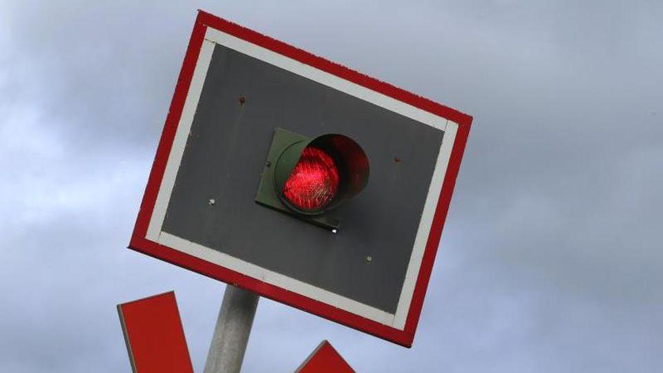 Eine Ampel an einem beschrankten Bahnübergang zeigt Rot. Foto: Karl-Josef Hildenbrand/Archiv