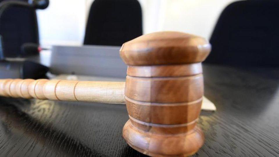 Auf einer Richterbank liegt ein hölzerner Richterhammer. Foto: Uli Deck/dpa/Archivbild