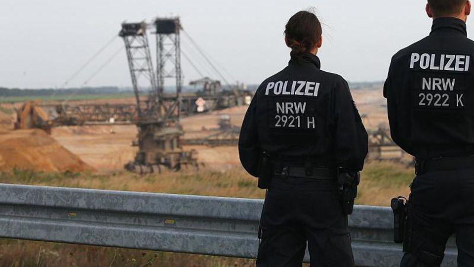 Polizisten stehen am Rande des Braunkohletagebaus Garzweiler. Foto: Oliver Berg/Archivbild