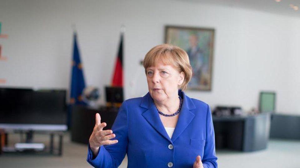 Merkel mit Herzchen-Kissen im Büro.
