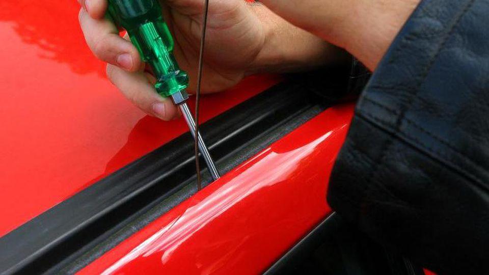 Eine Autotür wird mit Hilfe eines Schraubenziehers geöffnet (Symbolbild). Foto: Heiko Wolfraum/dpa/Archivbild