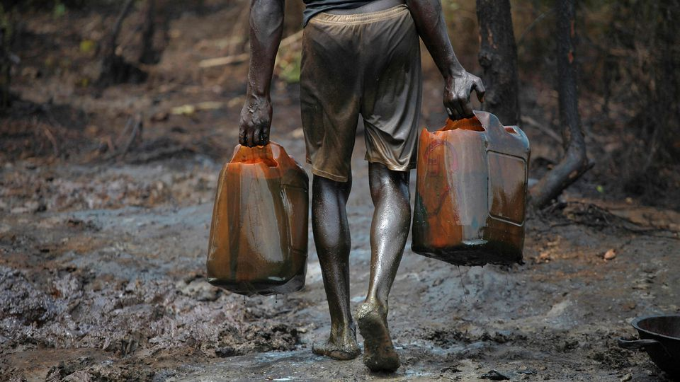 FILE PHOTO: A man works at an illegal oil refinery site near river Nun in Nigeria's oil state of Bayelsa November 27, 2012. REUTERS/Akintunde Akinleye/File Photo