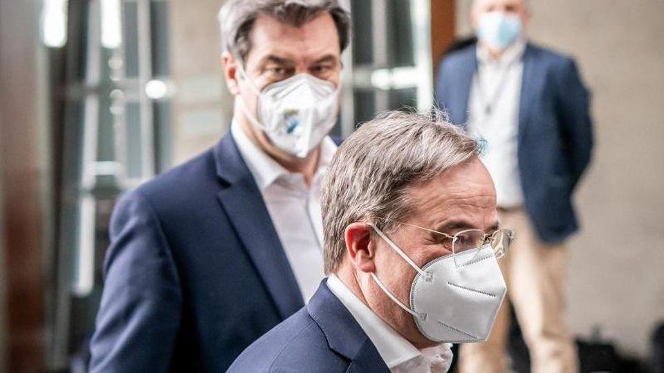 Markus Söder (CSU, hinten) und Armin Laschet (CDU)gehen zu einer Pressekonferenz. Foto: Michael Kappeler/dpa/Archivbild