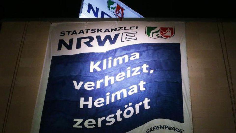 Greenpeace Aktivisten haben am Düsseldorfer Staatskanzlei zwei Banner aufgespannt. Foto: David Young/dpa