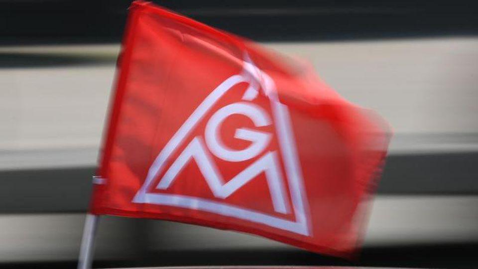 Eine rote IG-Metall-Flagge spiegelt sich in einem Fahrzeugdach. Foto: Patrick Seeger/Archivbild