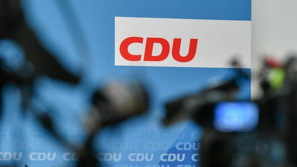 Hinter Fernsehkameras ist das Logo der CDU zu sehen. Foto: Jens Kalaene/zb/dpa