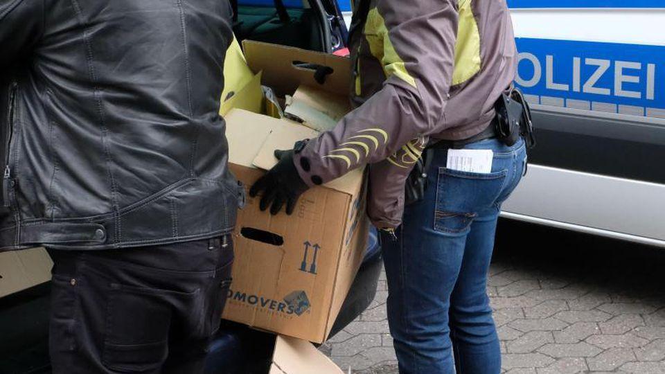 Zwei Polizeibeamte in Zivil stellen Kartons mit beschlagnahmten Unterlagen in einen PKW. Foto: Peter Steffen/dpa/Illustration