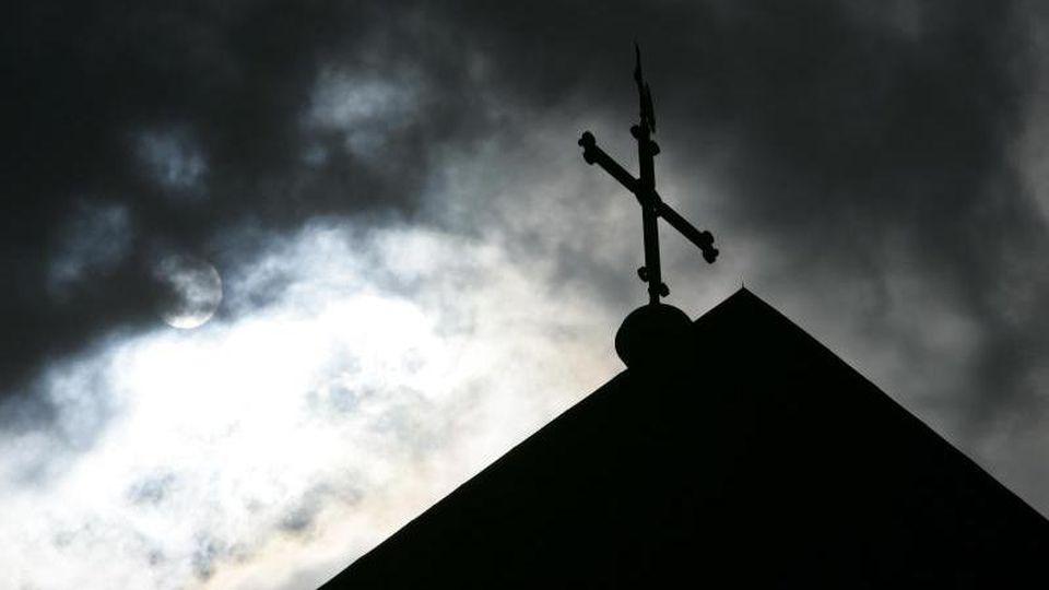 Im Gegenlicht und vor wolkenverhangenem Himmel ist die Kirchturmspitze eines Doms mit Kreuz zu sehen. Foto: Friso Gentsch/Archivbild