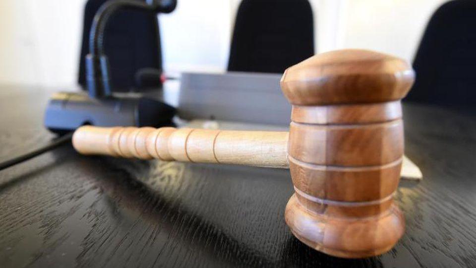 Auf der Richterbank liegt ein Richterhammer aus Holz. Foto: picture alliance / Uli Deck/dpa/Illustration