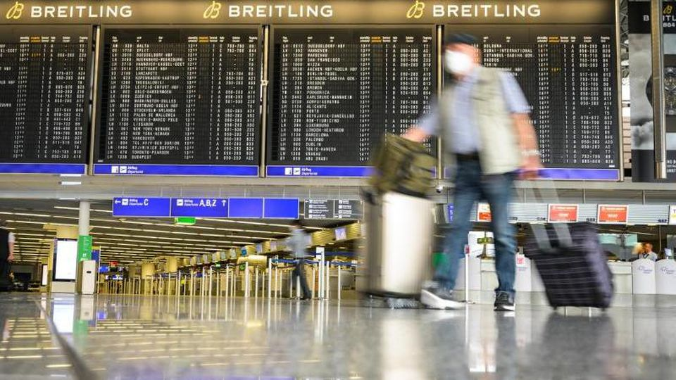 Reisende gehen mit Gepäck durch die Abflughalle im Terminal 1 am Flughafen Frankfurt. Foto: Andreas Arnold/dpa/Symbolbild