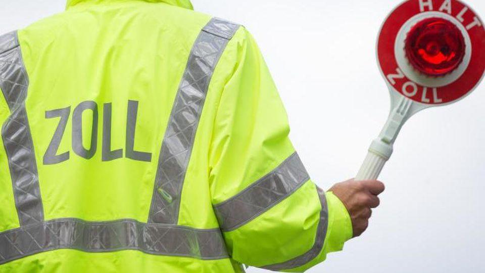 Ein Zollbeamter bittet darum, anzuhalten. Foto: Friso Gentsch/dpa/Symbolbild