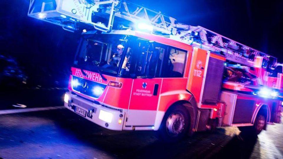 Ein Drehleiterwagen der Feuerwehr fährt mit Blaulicht an einer Unfallstelle vorbei. Foto:Marcel Kusch/Archiv