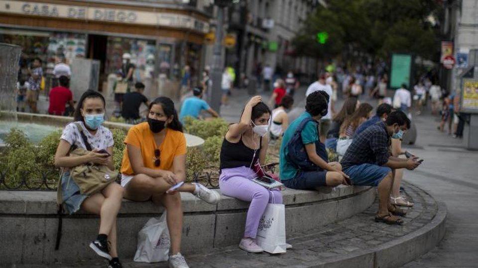 Menschen mit Masken in der Innenstadt von Madrid. Das Auswärtige Amt warnt wegen der Corona-Pandemie nun auch vor Reisen inSpaniens Hauptstadt Madrid. Foto: Manu Fernandez/AP/dpa