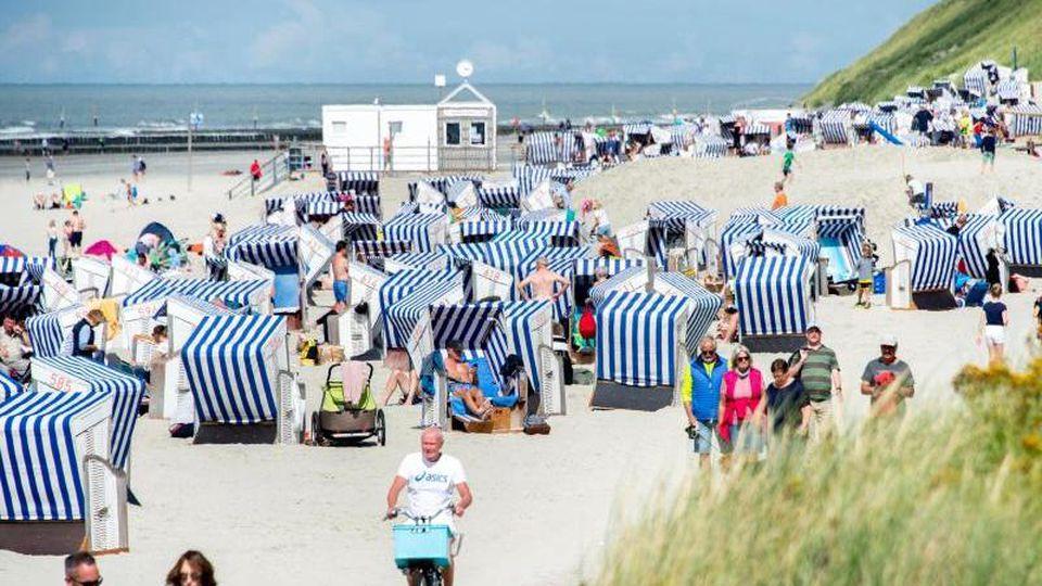 Urlaubsgäste sitzen bei sonnigem Wetter in ihren Strandkörben am Nordstrand der Insel Norderney. Foto: Hauke-Christian Dittrich/dpa