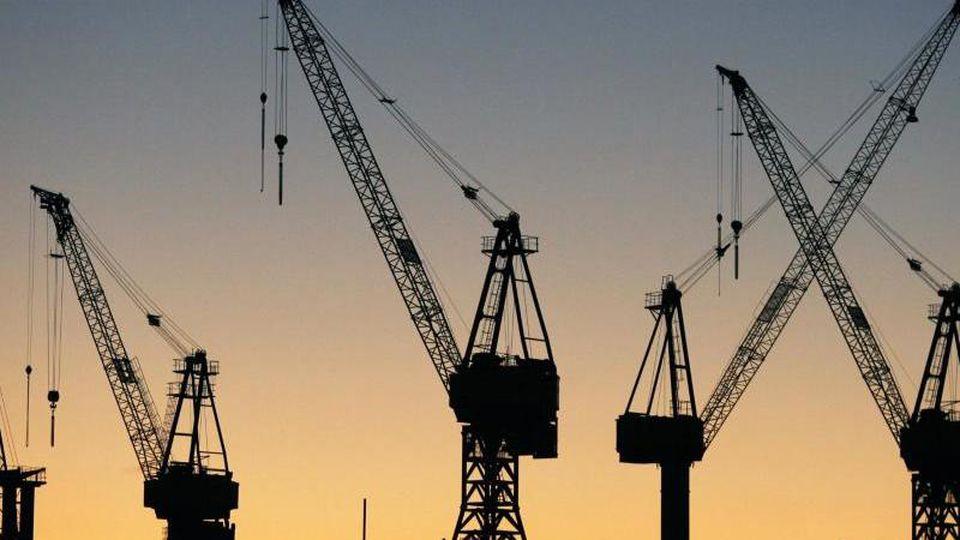 """Die Sonne geht hinter Kränen im Hamburger Hafen auf. Die """"Wirtschaftsweisen"""" haben ihre Wachstumsprognose für 2019 deutlich gekappt. Foto: Sebastian Widmann"""