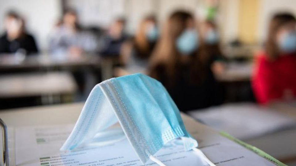 Eine Maske liegt im Unterricht auf Unterlagen. Foto: Matthias Balk/dpa/Illustration