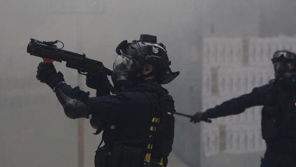 Ein Polizist zielt mit Tränengas auf Demonstranten bei regierungskritischen Protesten. Foto: Ng Han Guan/AP/dpa