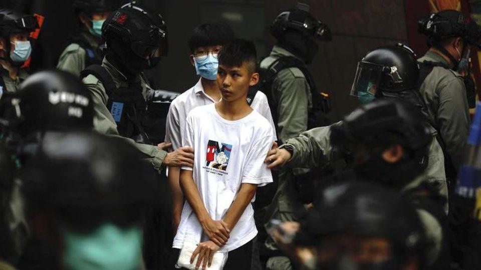 Bereitschaftspolizisten halten im Zentrum von Hongkong zwei junge Demonstranten fest. Foto: Kin Cheung/AP/dpa