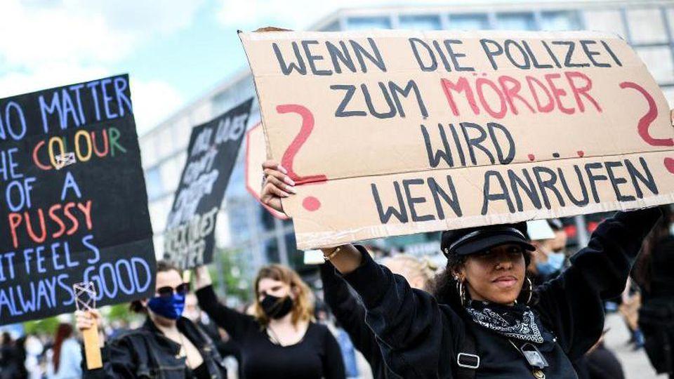 """Teilnehmer halten Schilder - u.a. mit der Aufschrift """"Wenn die Polizei zum Mörder wird wen anrufen?"""". Foto: Britta Pedersen/dpa-Zentralbild/dpa"""