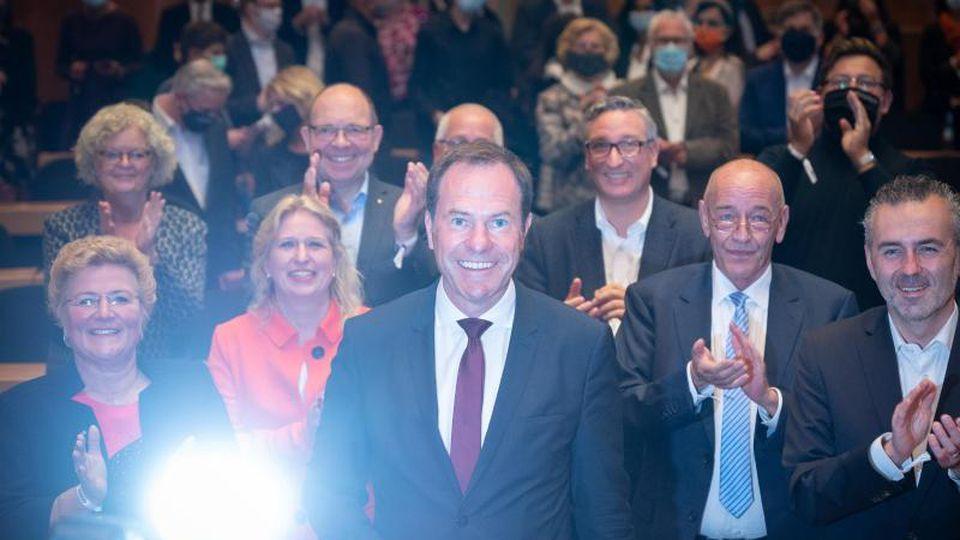 Stephan Keller (M), Oberbürgermeisterkandiat der CDU, freut sich zwischen Parteimitgliedern über die Auszählungen der Wahllokale. Foto: Bernd Thissen/dpa