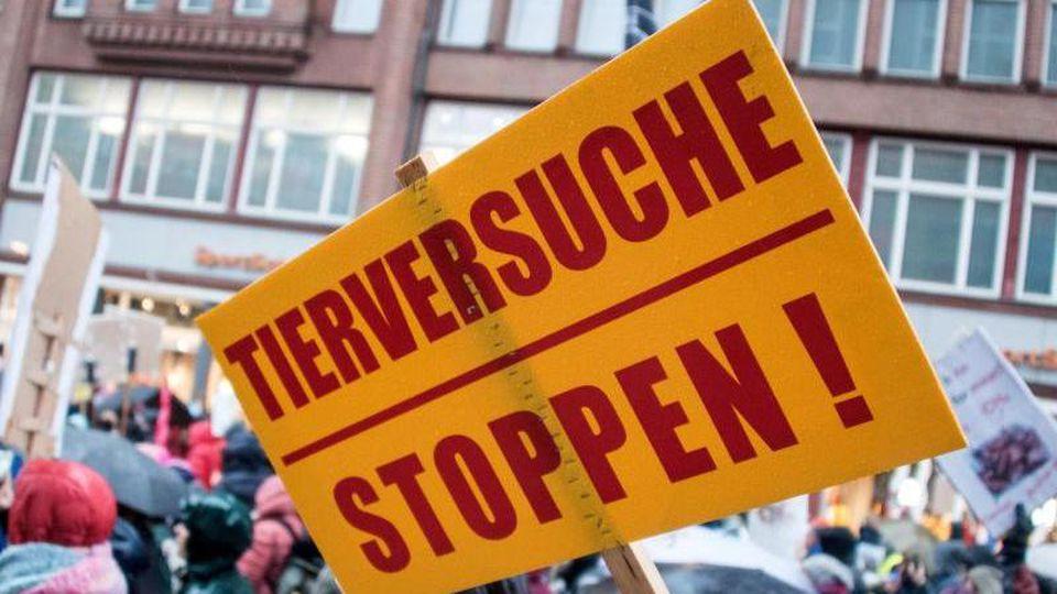 """Demonstranten ziehen mit einem Schild mit der Aufschrift """"Tierversuche stoppen!"""" durch Hamburg. Foto: Daniel Bockwoldt/dpa/Archivbild"""