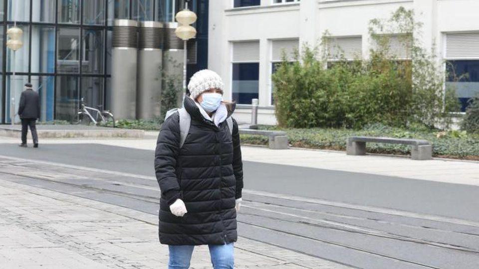 Eine Passantin läuft mit Mundschutz und Handschuhen durch Jenas Innenstadt. Foto: Bodo Schackow/dpa-Zentralbild/dpa