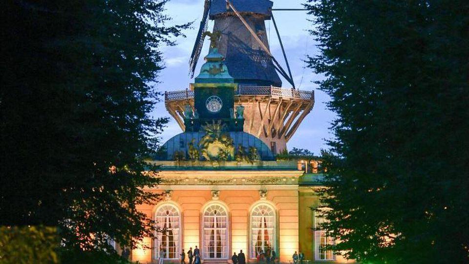 Farbig beleuchtet sind die Neuen Kammern und die Historische Mühle während der Potsdamer Schlössernacht im Park Sanssouci. Foto: Jens Kalaene