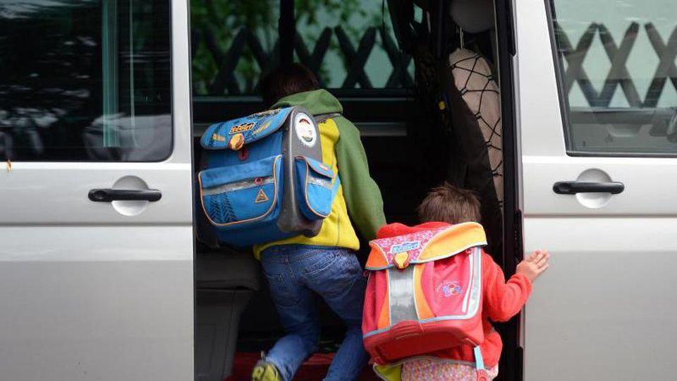 Schulkinder steigen in ein privates Fahrzeug. Foto: Ralf Hirschberger/zb/dpa/Archivbild