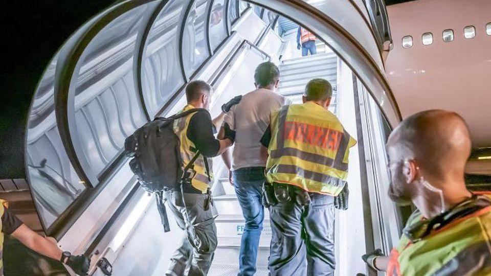 Polizeibeamte begleiten einen Mann in ein Charterflugzeug. Foto: Michael Kappeler/dpa/Symbolbild