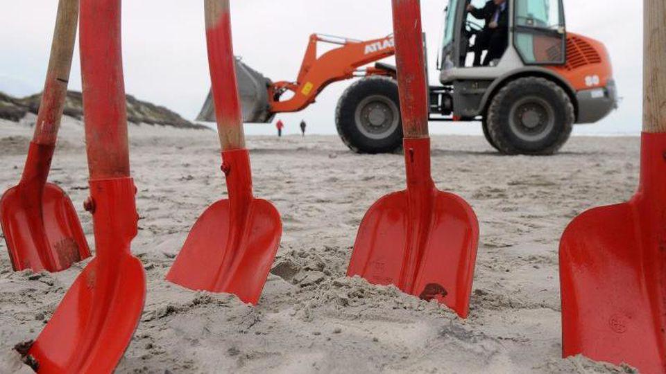 Rote Schaufeln stehen im Rahmen der Einweihung der neu aufgespülten Dünenlandschaft in Langeoog. Foto: picture alliance / dpa/Archivbild