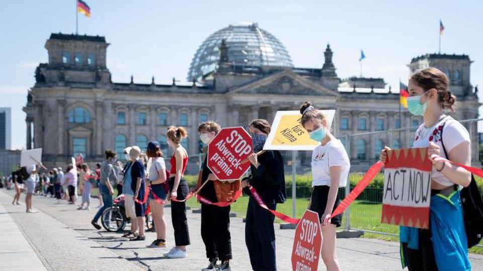 Aktivisten demonstrieren mit einer Menschenkette gegen eine mögliche Abwrackprämie. Foto: Kay Nietfeld/dpa