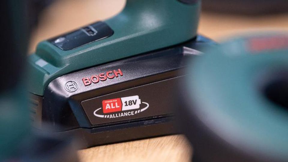 """Ein Akku mit dem Label """"Power for all 18 V Alliance"""" von Bosch steckt an einem Bohrer der Firma. Foto: Sebastian Gollnow/dpa"""