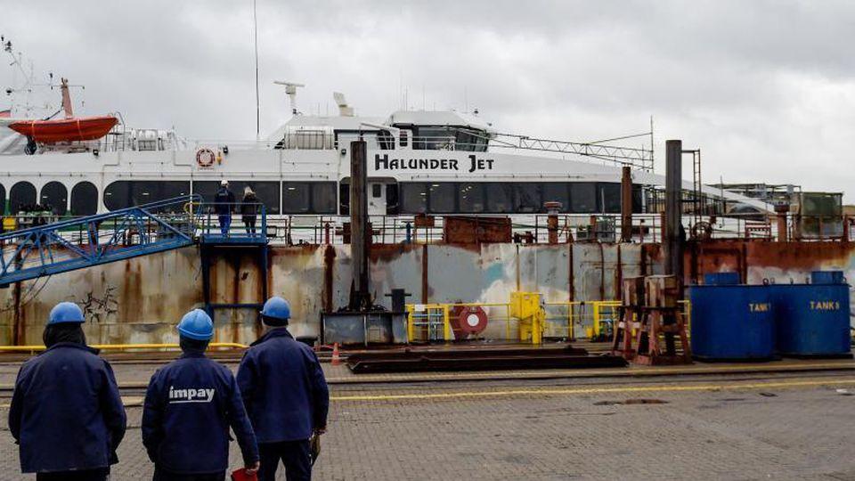 """Arbeiter gehen in der Hamburger Norderwerft auf den im Dock liegenden """"Halunder Jet"""" zu. Foto: Axel Heimken/Archiv"""