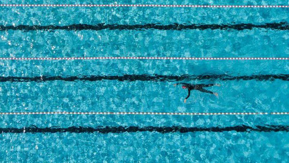 Ein Badegast schwimmt im Freibad in einem 50-Meter-Becken. Foto: Axel Heimken/dpa/Symbolbild