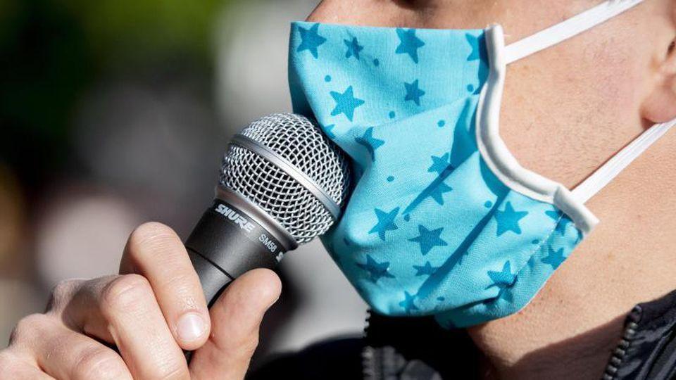 Ein Demonstrant spricht mit Mundschutz in ein Mikrofon. Foto: Christoph Soeder/dpa/Symbolbild