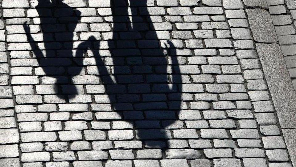 Die Schatten einer erwachsenen Person und eines Kindes sind zu sehen. Foto: Matthias Hiekel/zb/dpa/Illustration