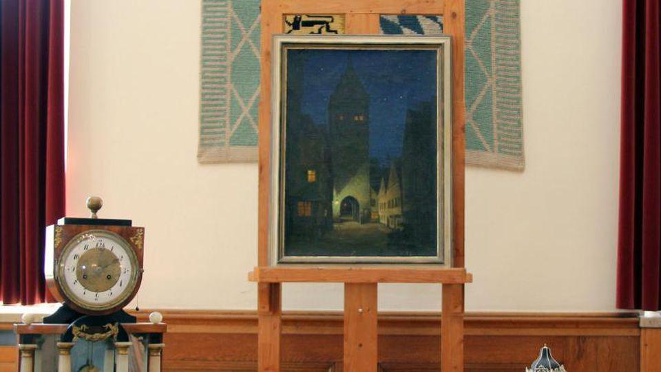 Eine Tischuhr (l-r), ein Gemälde des Memminger Künstlers Josef Madlener und eine Elfenbeinminiatur in Form eines Gartenpavillons stehen nebeneinander. Foto: Julia Mayer/Pressestelle Stadt Memmingen