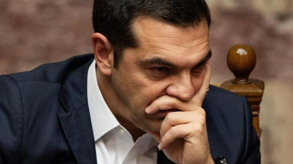 Der griechische Ministerpräsident Alexis Tsipras schaut während einer Parlamentssitzung nachdenklich in die Runde. Foto: Angelos Tzortzinis