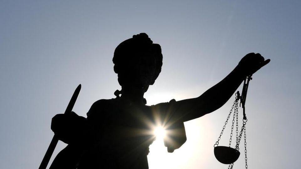 Die Statue der Justitia mit einer Waage und einem Schwert in der Hand. Foto: Arne Dedert/dpa/Symbolbild
