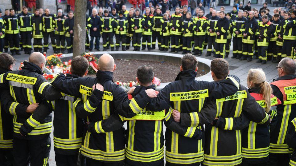 dpatopbilder - 08.12.2019, Bayern, Augsburg: Am Königsplatz trauern Feuerwehrmänner. Ein Feuerwehrmann war am Abend des 06.12.2019 in seiner Freizeit hier in einer Auseinandersetzung mit einer Gruppe so schwer verletzt worden, dass er starb. Foto: St