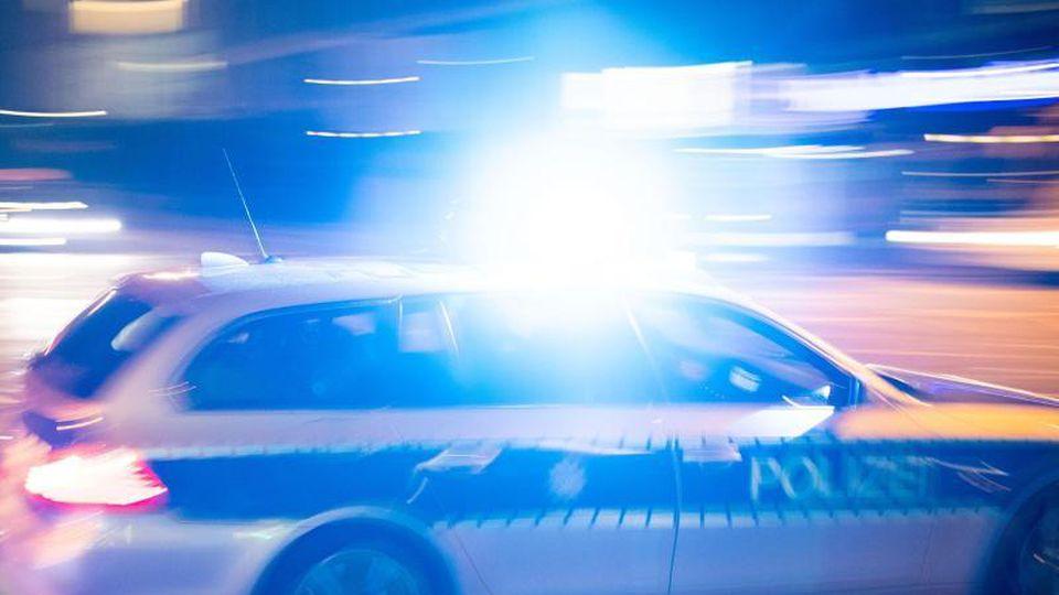Ein Polizeiauto fährt unter Einsatz von Blaulicht und Sirene eine Straße entlang. Foto: Lino Mirgeler/dpa/Archiv/Illustration